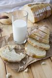 a glass of milk and cut bread on a wooden table stock photos