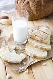 a glass of milk and cut bread on a wooden table and scattered stock image