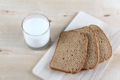 Glass of milk and dark bread Stock Photography