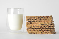 Glass of milk and dry bread. On grey background Stock Image