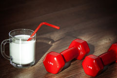 Glass of milk and dumbbells Royalty Free Stock Photos
