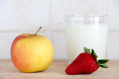 A glass of milk with fresh fruits. A composition with a glass of milk with fresh fruits, a big strawberry and an apple, on a wooden chopping board, inside a Stock Image