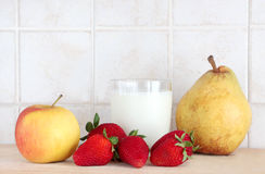A glass of milk with fresh fruits. A composition with a glass of milk with fresh fruits, some strawberries, a pear and an apple, on a wooden chopping board royalty free stock images