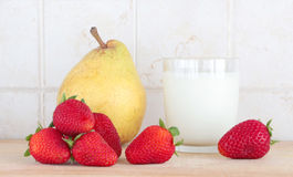 A glass of milk with fresh fruits. A composition with a glass of milk with fresh fruits, some strawberries and a pear, on a wooden chopping board, inside a Royalty Free Stock Images