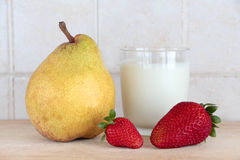 A glass of milk with fresh fruits Royalty Free Stock Photos