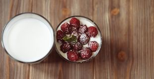 A glass of milk and granola with raspberries over wooden background, top view, close up. Happy breakfast Royalty Free Stock Images