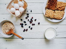glass of milk, home-made cake, eggs, rose hips and oat flakes in a plate on white table Royalty Free Stock Photos