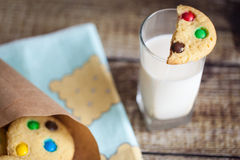 A glass of milk and homemade cookies. With color candies in cornet on wood background Royalty Free Stock Photos