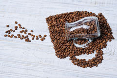 Glass milk jug and coffee beans Royalty Free Stock Images
