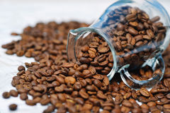 Glass milk jug and coffee beans Royalty Free Stock Photography