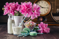 Glass of milk with macaroons on wooden table Stock Image