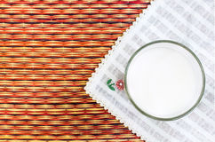 Glass of milk on Natural straw made floor mate background.  royalty free stock photography