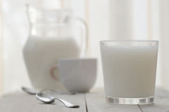 A glass of milk next to a jar and a cup Stock Image
