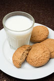 Glass of milk and oat cookies on a plate Stock Image