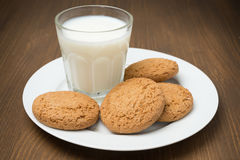 Glass of milk and oat cookies on a plate, horizontal Royalty Free Stock Photo