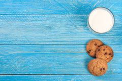 Glass of milk with oatmeal cookies on a blue wooden background with copy space for your text. Top view. Glass of milk with oatmeal cookies in a wicker basket on stock image