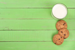 Glass of milk with oatmeal cookies on a green wooden background with copy space for your text. Top view Royalty Free Stock Photos