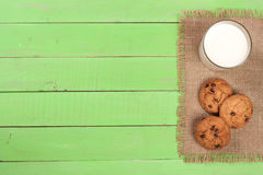 Glass of milk with oatmeal cookies on a green wooden background with copy space for your text. Top view Royalty Free Stock Image