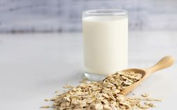 A glass of milk and oats in spoon on the white table. Its are a nutrient-rich food associated with protein and fiber.  stock image