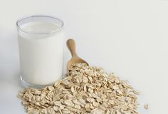 A glass of milk and oats in spoon on the white table. Its are a nutrient-rich food associated with protein and fiber.  royalty free stock photography