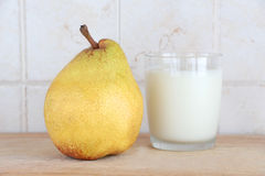 A glass of milk and a pear. A composition with a glass of milk and a pear, on a wooden chopping board, inside a kitchen, landscape cut royalty free stock photo
