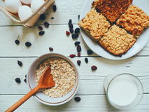 glass of milk, a piece of homemade cake, eggs and oatmeal in a bowl Stock Photo