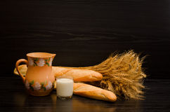 A glass of milk, a pitcher, and loaves sheaf on a black background. With space for text stock photo
