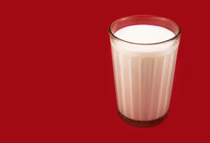 Glass with milk on the red stock image