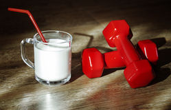 Glass of milk and red dumbbells Stock Images