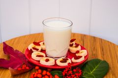 A glass of milk on a red saucer. Chopped banana and goji berries Stock Images