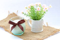 Glass of milk with ribbon on sack over white. Royalty Free Stock Images