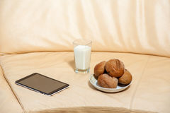 Glass of milk with rolls lie on the couch Royalty Free Stock Photos