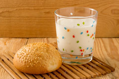 A glass of milk with sesame bun. S on wood background Stock Photos