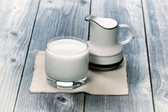 Glass of milk and small pitcher on age wood Stock Images