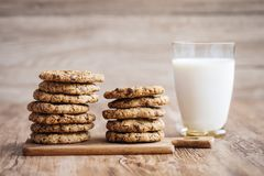 Milk and cookies, homemade with chocolate chips. A glass of milk and some homemade cookies, with melted chocolate chips. The cookies are piled up on a on a stock photos