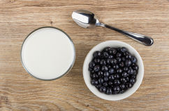 Glass of milk, spoon and bowl with blueberries on table Royalty Free Stock Photo