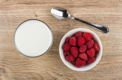 Glass of milk, spoon and bowl with raspberries on table Royalty Free Stock Images