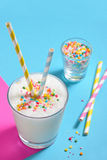 Glass of milk with striped straws stock image