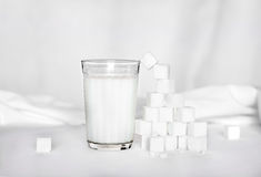 Glass of milk and sugar. Glass of milk and pieces of sugar on a light background Royalty Free Stock Images