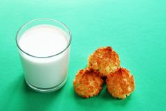 Glass of milk and three cookies on a turquoise background. royalty free stock image