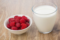 Glass of milk and white bowl with raspberries on table. Glass of milk and white bowl with raspberries on wooden table Royalty Free Stock Images