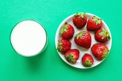 Glass of milk and white saucer with ripe red strawberry on a turquoise background, top view. Healthy summer food royalty free stock photos