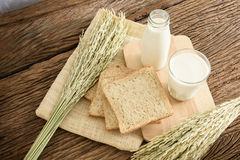 Glass of milk and whole wheat bread on the wooden board