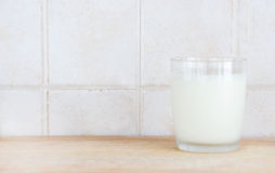 A glass of milk on a wooden chopping board. A composition with a glass of fresh milk on a wooden chopping board, inside a kitchen, space for text on the left Royalty Free Stock Images