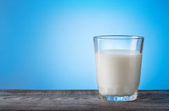 Glass of milk on wooden table with blue background Stock Image