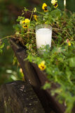 Glass of milk on the wooden wagon surrounded by flowers. Vertical Royalty Free Stock Photo