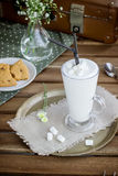 Glass with milkshake  and cookie in cafe. Royalty Free Stock Images