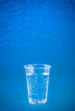 Glass of mineral water on a blue background Royalty Free Stock Photos
