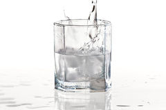 Glass of mineral water and ice with splash Stock Photo
