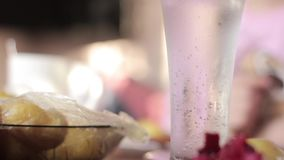 Glass with mineral water on a table, rural breakfast from baked potato and sausages stock footage